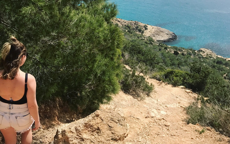 girl walking down cliff to beach